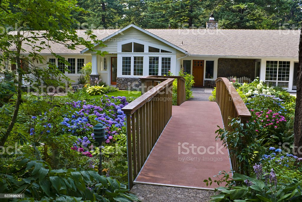 Bridge leads to Ranch Home surrounded by colorful hydrangea Gardens stock photo