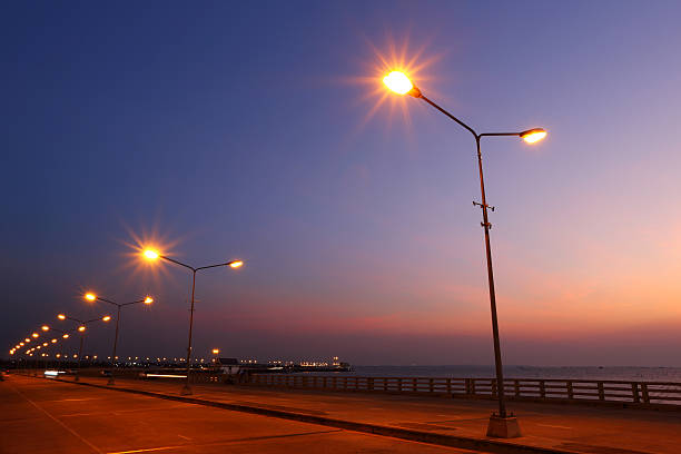 Bridge lights lit in the sunset stock photo