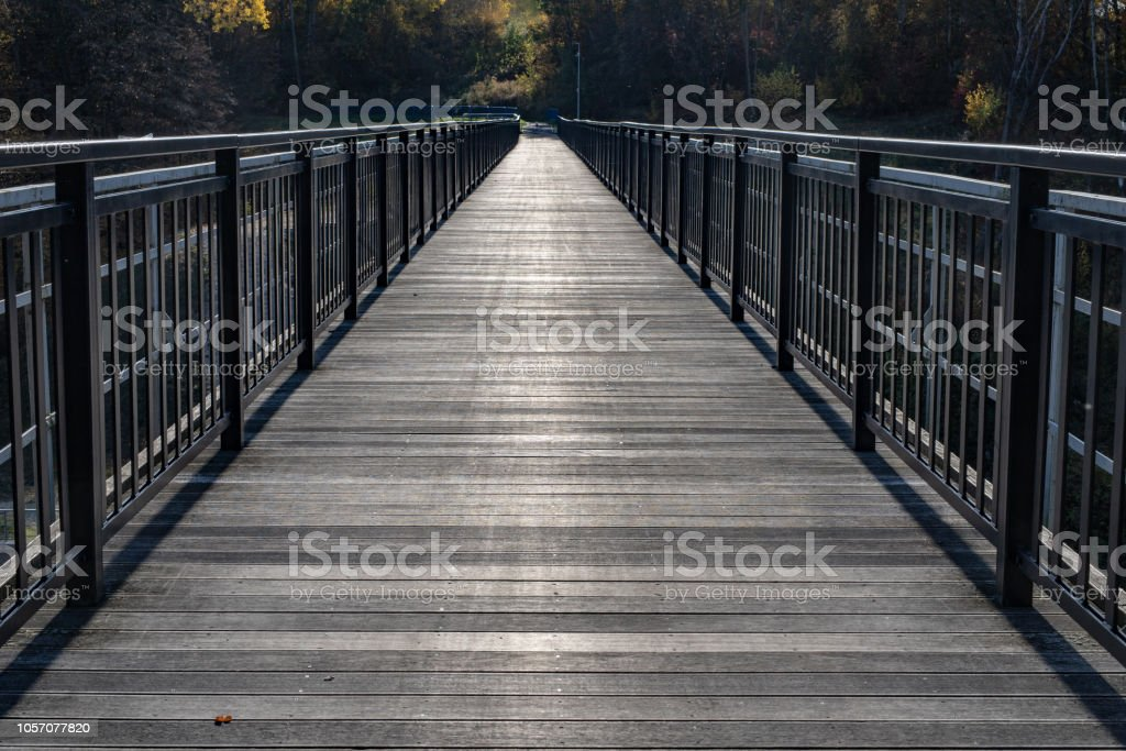 A bridge made of planks in central europe. Crossing the river built on a lattice from the narrow-gauge railway bridge. Season of the autumn. stock photo
