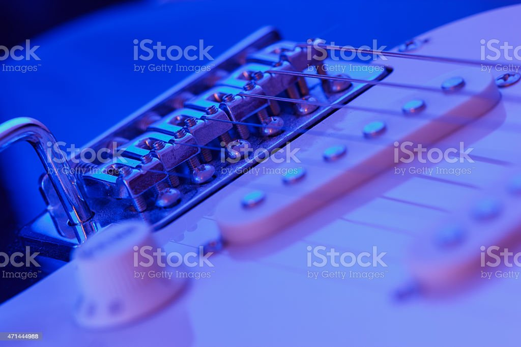 Bridge of an electric guitar with blue light stock photo