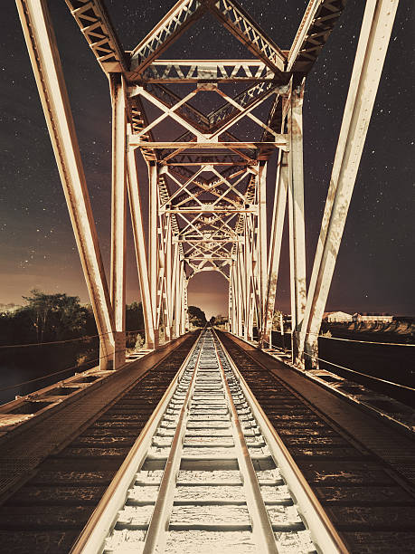 Bridge of the Railroad A railway bridge spanning a small river at night.  Long exposure with light painting. railway bridge stock pictures, royalty-free photos & images