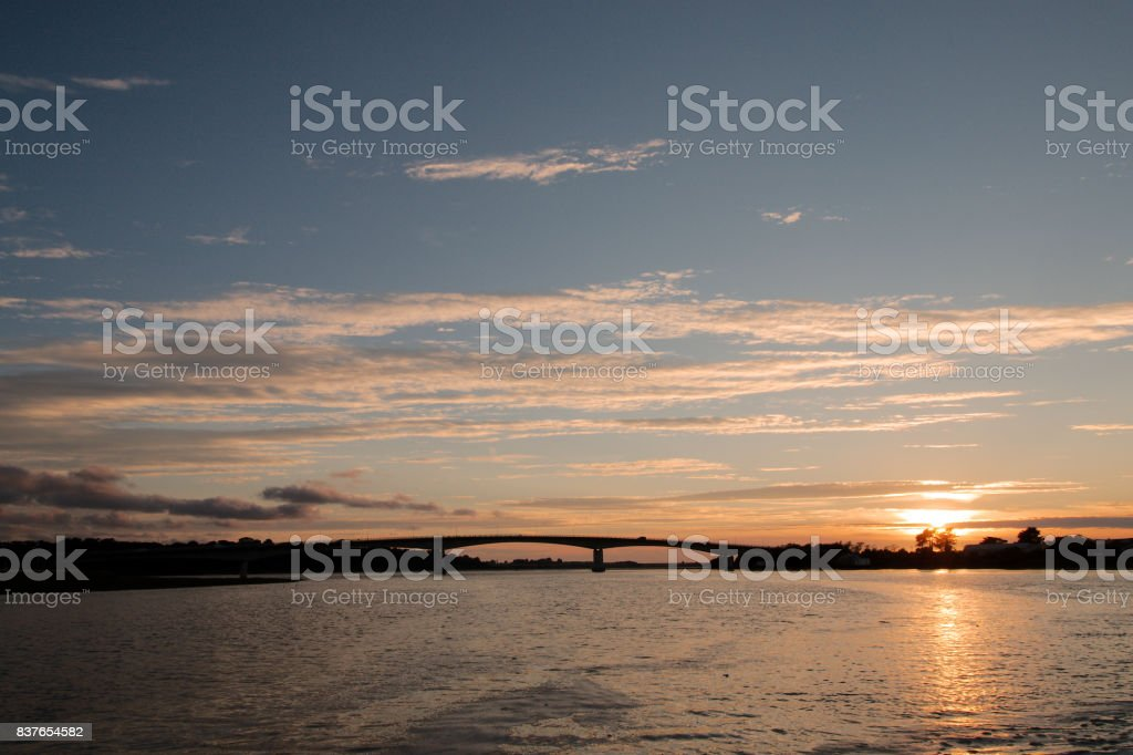 A bridge over a river estuary at sunset. stock photo