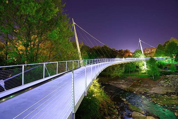 Bridge over Falls Park at night Liberty Bridge at Falls Park in Greenville, South Carolina. liberty bridge budapest stock pictures, royalty-free photos & images