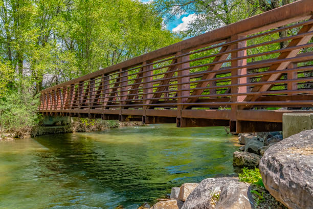 Bridge over glistening river with rocks on the bank at Ogden River Parkway stock photo
