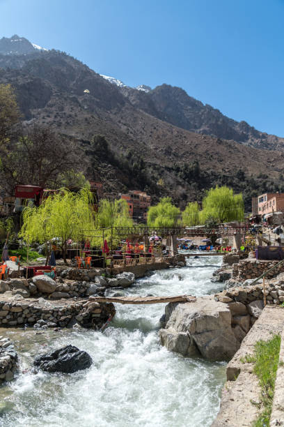 Bridge over stream with cafe seating in a Berber Village - High Atlat Mountains stock photo