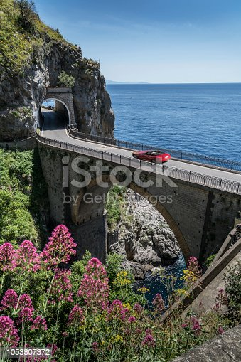 Italy. Amalfi Coast. A red sport car over the narrow bridge over the fjord of Furore.