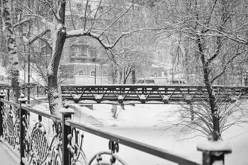 Bridge over the frozen river, covered with snow