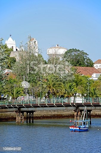 Footbridge across the River Gilao with town buildings to the rear, Tavira, Algarve, Portugal, Europe.