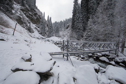 bridge over the river in the mountains in winter