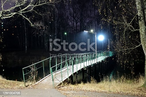 istock Bridge over the river with lanterns at night. Loneliness. Winter time 1291004705