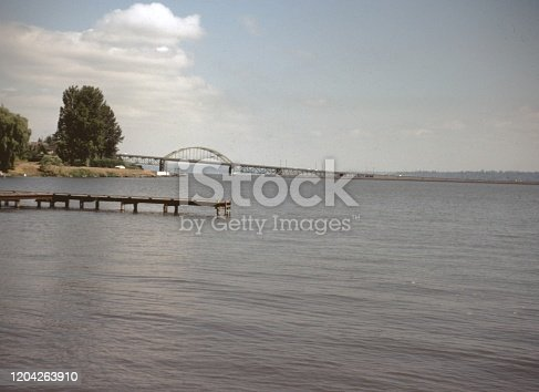 Vernacular photograph taken on a 35mm analog film transparency, believed to depict bridge over the sea during daytime, 1965. Major topics/objects detected include Water, Water Resources, Sky, Bridge, River, Lake, Sea, Tree, Pier, Shore, Nature and Gray Color. (Photo by Smith Collection/Gado/Getty Images)