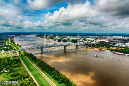 A tug boat moving toward a bridge spanning the mighty Mississippi River in southern Louisiana near New Orleans.
