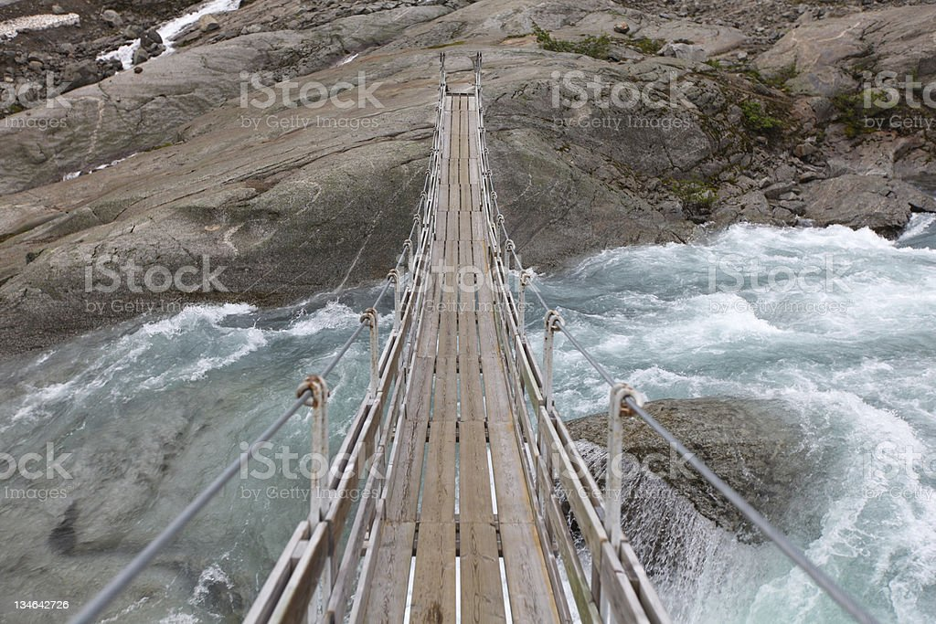 Bridge over troubled glacial water stock photo