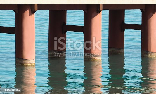 Bridge pillars with water reflection. Construction background