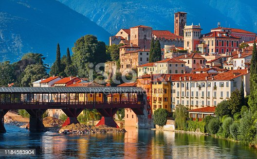 Bridge Ponte degli Alpini at river Brenta Bassano del grappa Italy. Panoramic view at old town with vintage building and tower and wooden bridge at background Alpine mountains scenic landscape evening