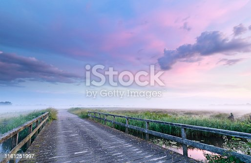 bridge road at beautiful misty pink sunrise, Netherlands