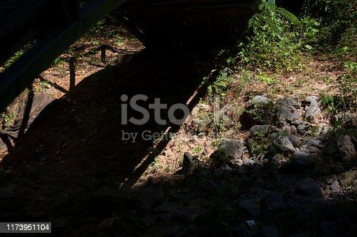 Shadow of a bridge falling across the rocky shore of a creek