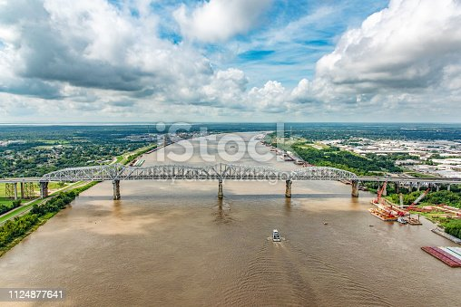 A bridge supporting both vehicles and a railway crossing the Mississippi River which is flanked on both sides by various industry located just north of New Orleans, Louisiana, shot from an altitude of about 600 feet over the river.