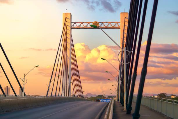 Brücke Sérgio Motta von Cuiabá mit Wolken durch den Sonnenuntergang im Hintergrund beleuchtet. – Foto
