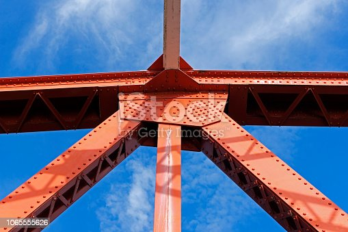 Close up view of a bridge support against a blue sky.