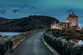 Dornie,Scotland,United Kingdom - November 12th, 2018: Stone Bridge towards the famous illuminated Eilean Donan Castle - the well known 'Highlander Castle' . The Eilean Donan Castle is build on a small islet in Loch Alsh in the Highland Region of Scotland at Twilight. Scotland, United Kingdom, Europe