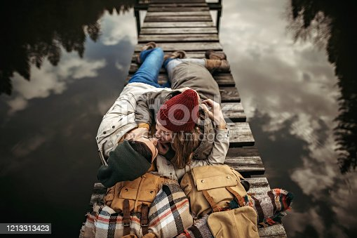 Hipster couple sitting on dock over the lake