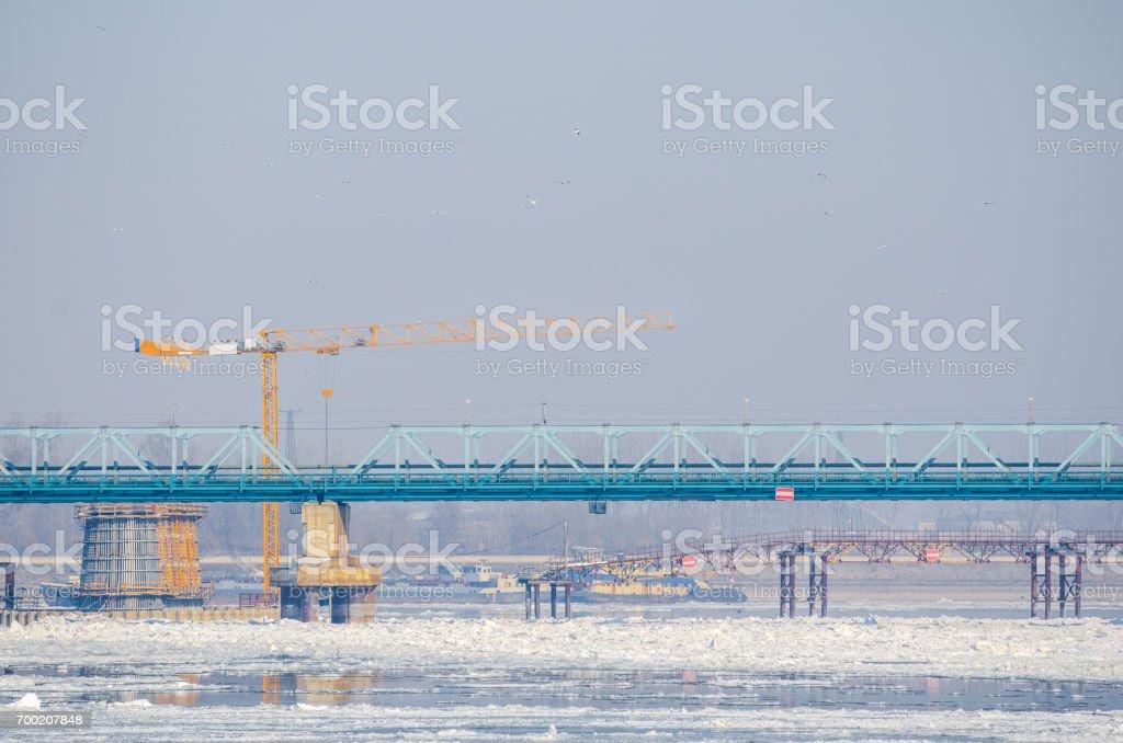 Bridge under construction over frozen river. Construction crane. stock photo