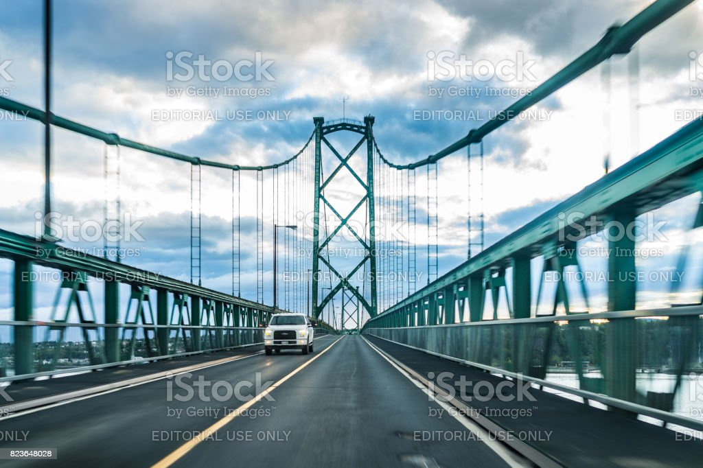 Bridge view crossing Saint Lawrence river from Ile D'Orleans, Quebec to Boischatel during sunset stock photo