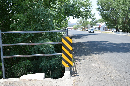 A black and yellow striped sign warns of road abutment.