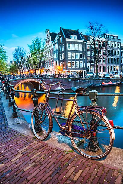 Puente y canal de agua con bicicletas en Amsterdam en la noche - foto de stock