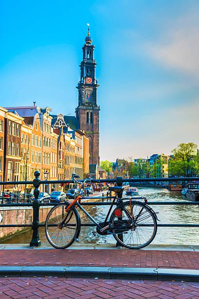 bridge with bicycle and water channel in amsterdam - westerkerk stockfoto's en -beelden