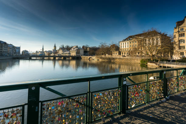 bridge with many locks symbolizing love in Zurich in Switzerland on the river Limmat many different color and style locks and the wire railing of a bridge symbolizing long relationships and everlasting romantic love limmat river stock pictures, royalty-free photos & images