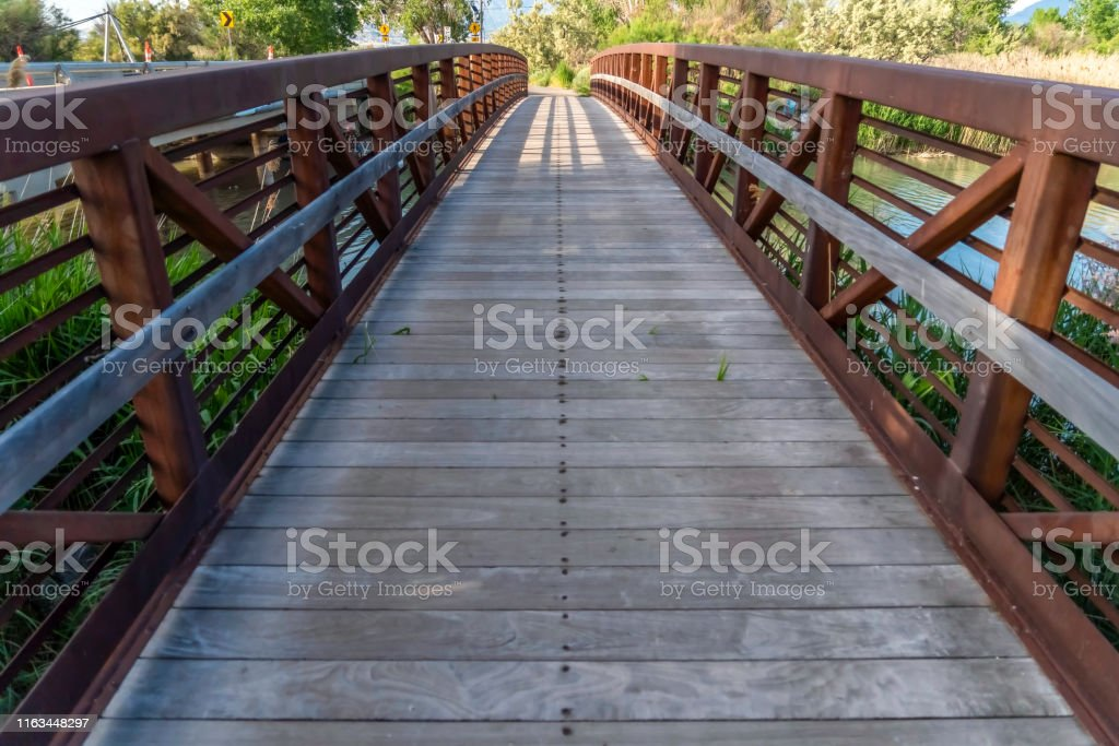 Bridge with wood deck and rusty metal railing over a lake with grassy...
