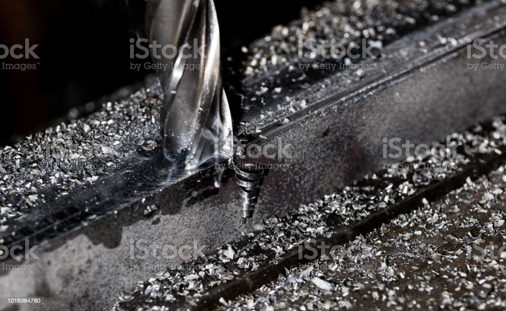 Bridgeport CNC end mill finishing a stack of steel plate with metal filings chips and smoke stock photo