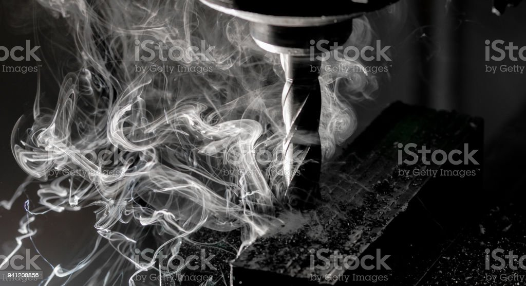 Bridgeport CNC end mill finishing a stack of steel plate with metal filings chips and heavy smoke trailing stock photo
