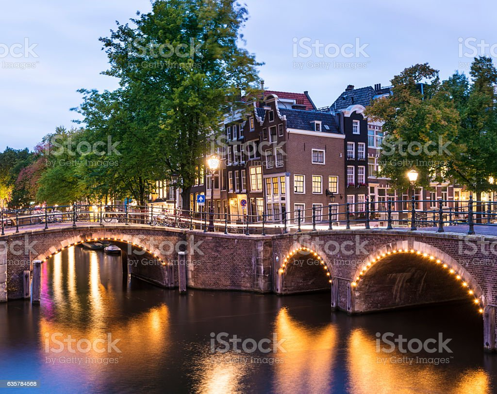 Bridges and canal houses illuminated at twilight in Amsterdam, Holland stock photo