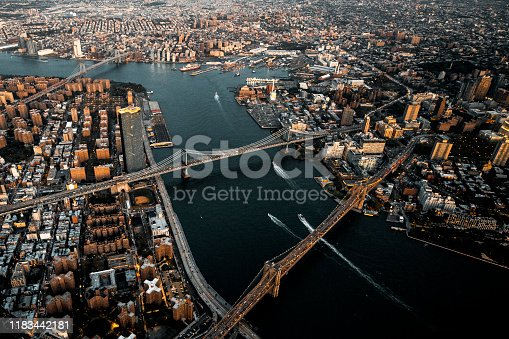 Brooklyn Bridge, Manhattan Bridge, and Williamsburg Bridge over the East River connecting Manhattan Island to Brooklyn, NYC, taken from a helicopter at golden hour.