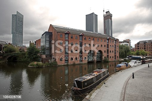 Bridgewater canal with narrow boats, Well pharmacy headquarters and Bentham tower in the background.
