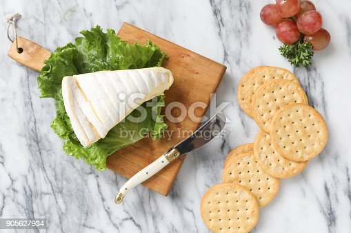 An overhead close up horizontal photograph of a wedge of brie cheese on a small wooden cutting board, crispy crackers and a few red grapes.