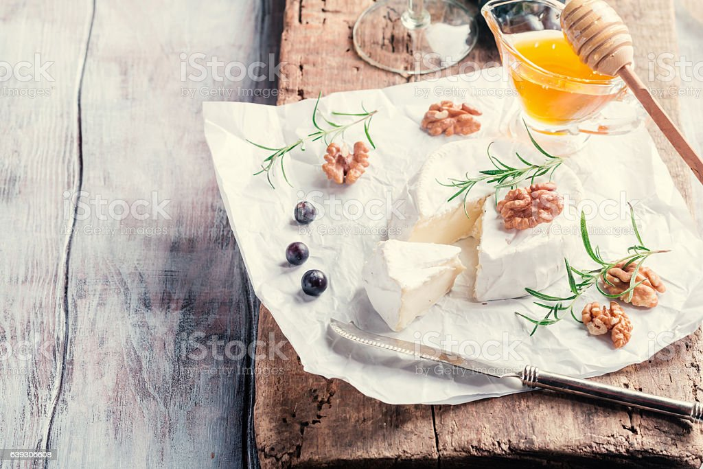 Brie cheese and slice on a wooden board - Photo