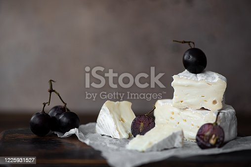 Brie cheese with black grapes on a wooden board