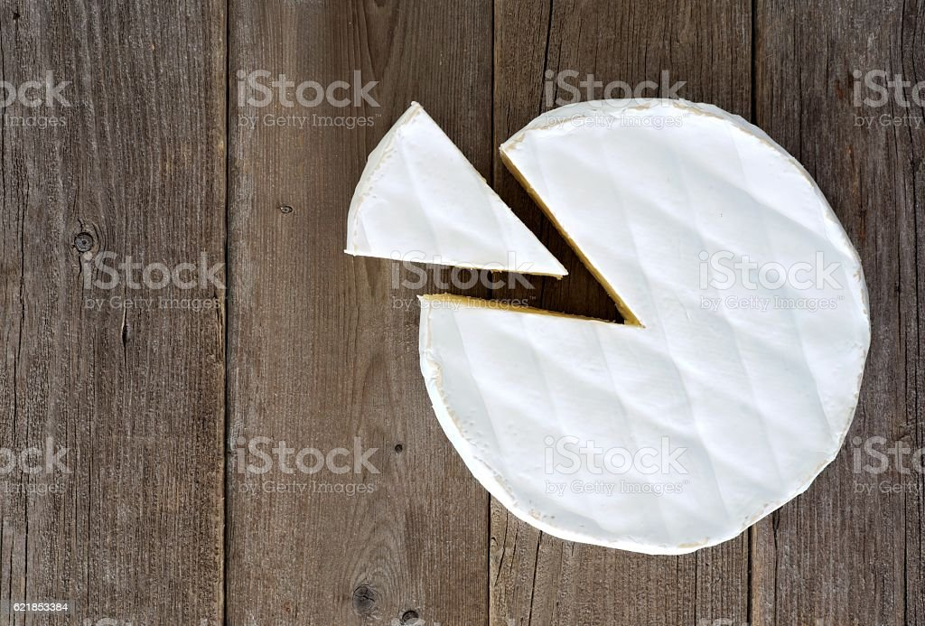 Brie cheese with cut slice, above view on rustic wood - Photo