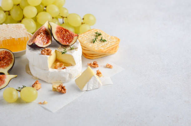 Brie or camembert cheese with figs, grapes, honey and nuts. stock photo
