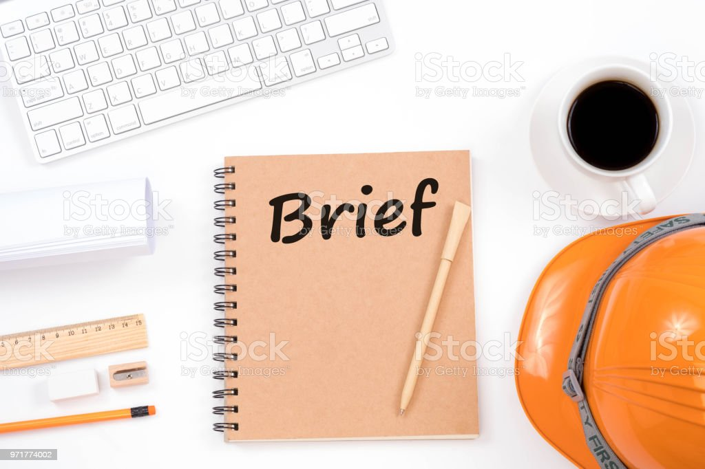 Brief concept. Top viwe of modern workplace with safety helmet, office supplies, a cup of coffee and keyboard on white background. stock photo