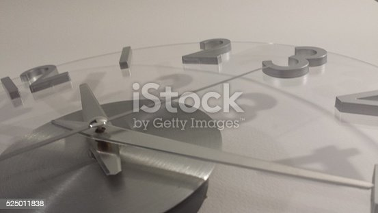 Brief time concept, contemporary clock face with metallic looking numbers and hands.