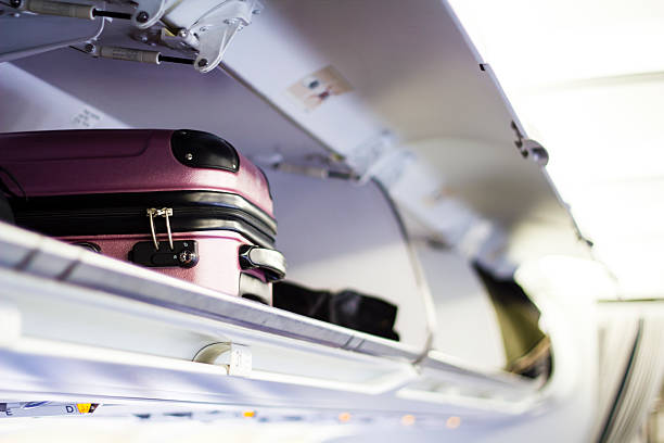 Briefcase in the plane Suitcase in the open log of the airplane cabin passenger cabin stock pictures, royalty-free photos & images