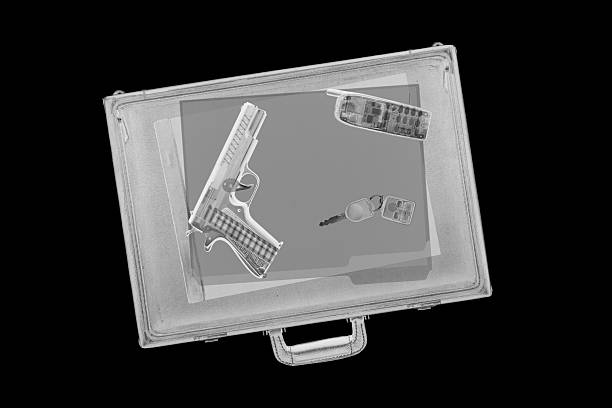 Briefcase with Gun XXL. Airport x-ray image of a briefcase with a handgun inside. gchutka stock pictures, royalty-free photos & images