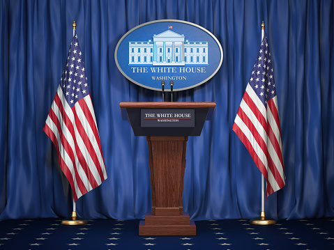 istock Briefing of president of US United States in White House. Podium speaker tribune with USA flags and sign of White Houise. Politics concept. 1021174468