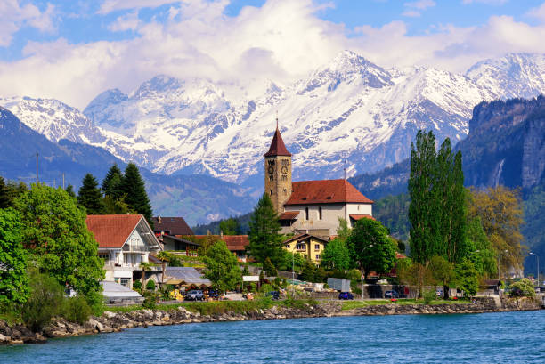Brienz town near Interlaken and snow covered Alps mountains, Switzerland Brienz town on Lake Brienz by Interlaken, Switzerland, with snow covered Alps mountains in background swiss alps stock pictures, royalty-free photos & images