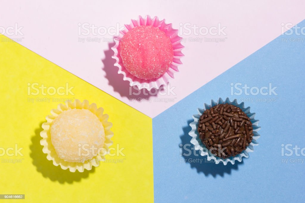 Brigadeiro Beijinho and Bicho de Pe: sweets from Brazil. Child birthday party. Flat design of candy ball on color background. stock photo